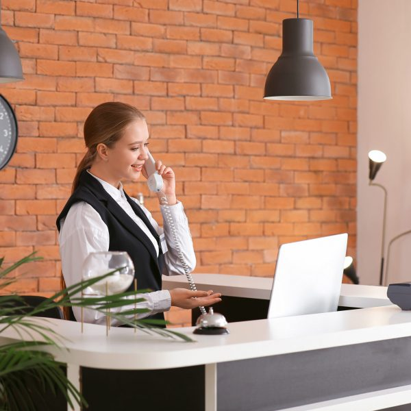 Young female receptionist talking by telephone at desk in hotel